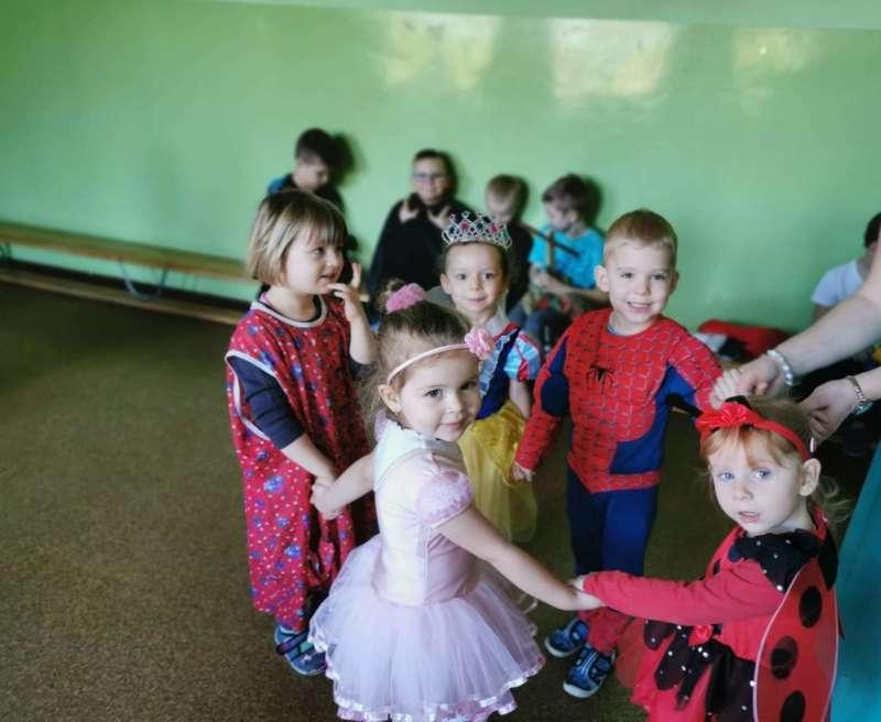 Dzieci przebrane w stroje bohaterów z filmów i bajek trzymają się za ręce i tańczą na szkolnym korytarzu.