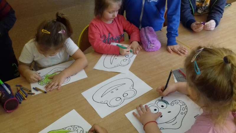 Dzieci siedzące przy stole kolorują obrazki z rysunkiem żaby.