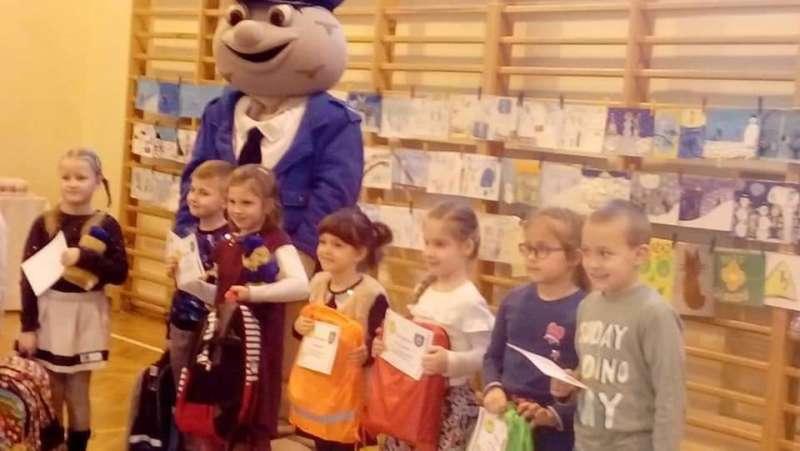 Dzieci stoją w rzędzie na sali gimnastycznej trzymając otrzymane w konkursie nagrody oraz dyplomy.