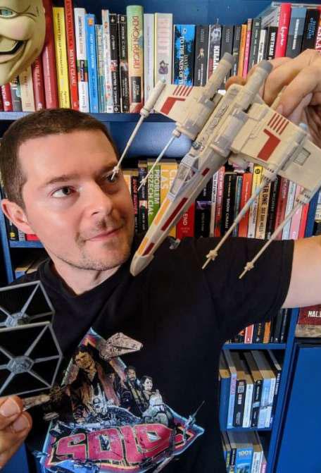 """Łukasz Nieradko trzyma w dłoniach makiety statków kosmicznych z filmu """"Gwiezdne Wojny""""."""