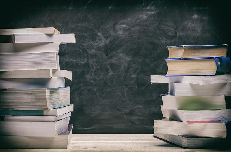 Dwa stosy podręczników ułożone na stole. W tle czarna tablica kredowa.