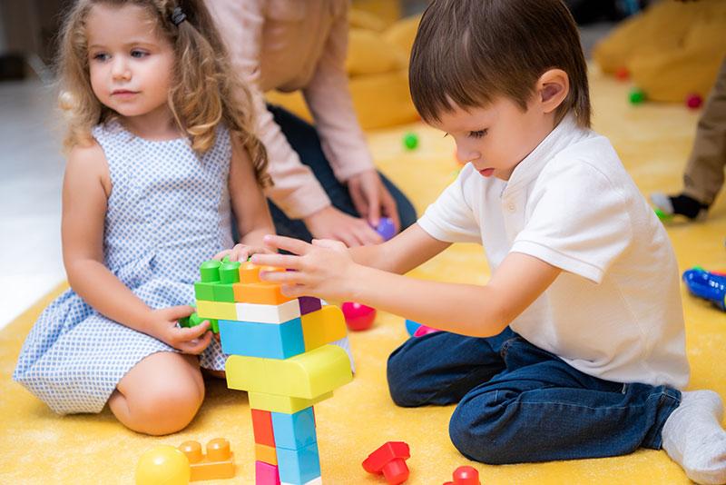 Dzieci układające na podłodze kolorowe klocki.