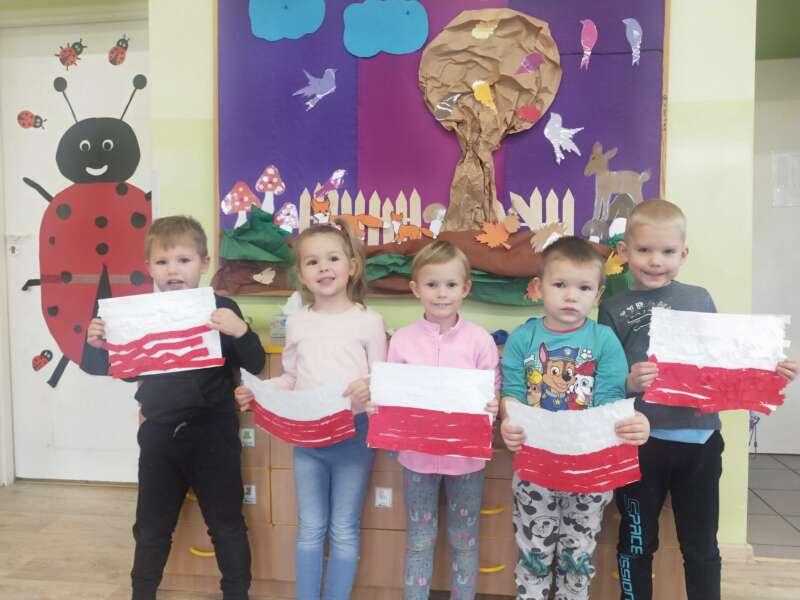 Dzieci prezentują biało-czerwone flagi, wykonane własnoręcznie z okazji Narodowego Święta Niepodległości
