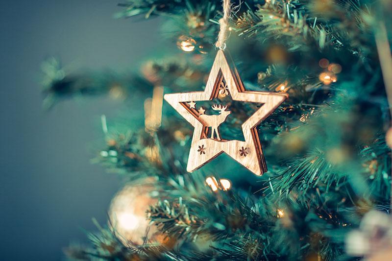 Bombka świąteczna w kształcie gwiazy wisząca na choince.