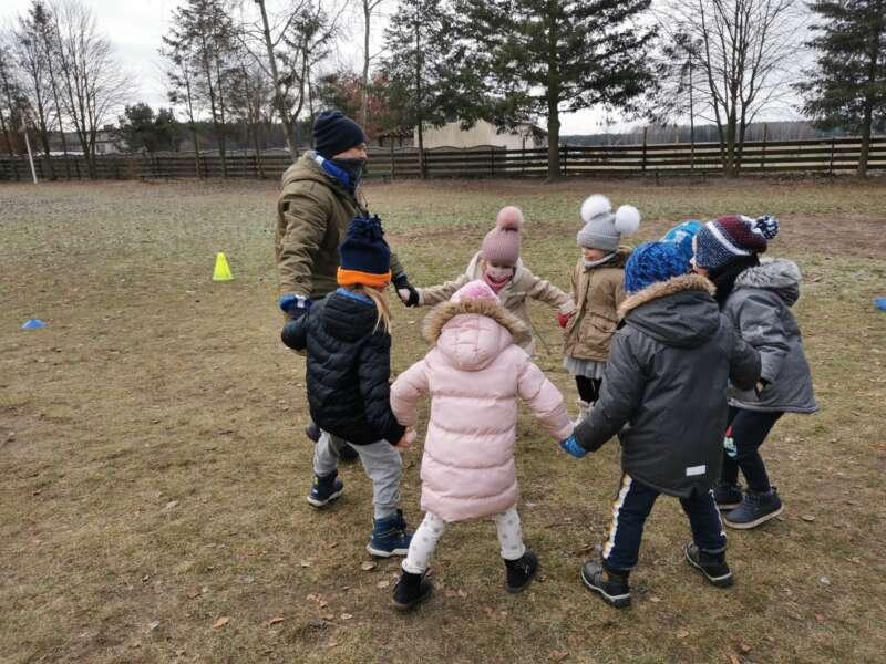 Dzieci bawią się w kółko graniaste na boisku szkolnym.