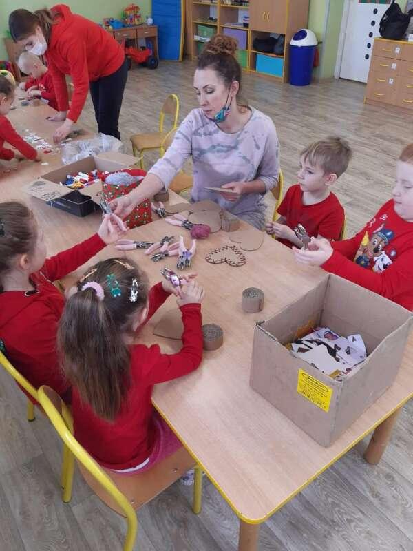 Dzieci siedzące przy połączonych stołach w klasie wykonują ozdoby walentynkowe.