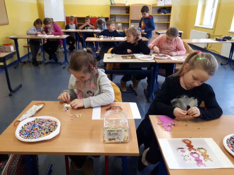 Dzieci siedzące przy stołach w klasie podczas zabawy z pysslą