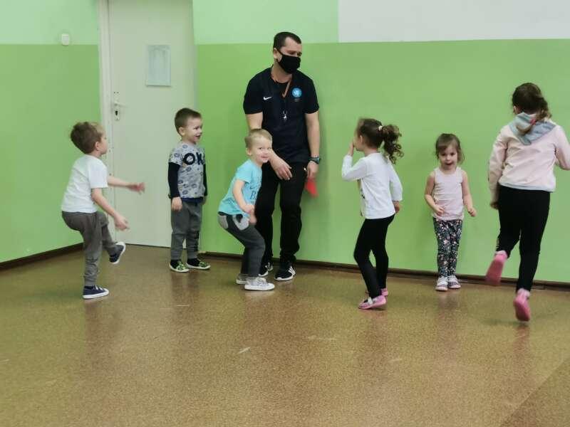 Dzieci podczas zabaw ruchowych z opiekunem na sali gimnastycznej.
