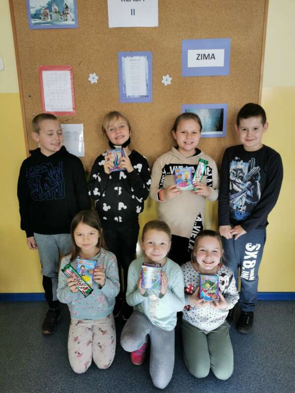 Szczęśliwe dziewczynki pozują do zdjęcia z łakociami, które otrzymały od chłopców.