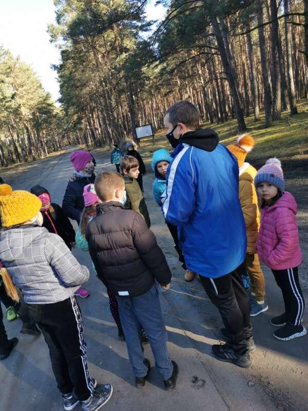 Dzieci podczas zabawy w podchody w lesie.