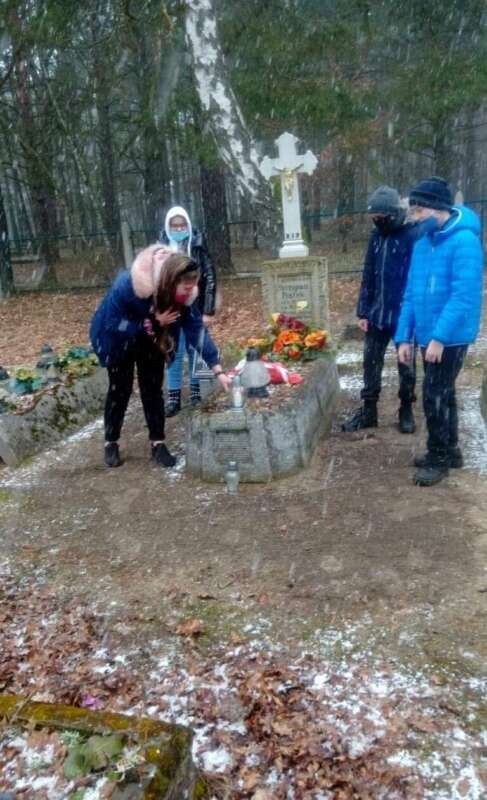 Uczniowie klasy VI zapalają znicze na grobach powstańców wielkopolskich.