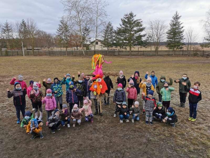Dzieci stojące w zimowych ubraniach na boisku szkolnym, pozują do zdjęcia z Marzanną
